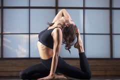 Young woman in One Legged King Pigeon pose, evening practice Royalty Free Stock Photos