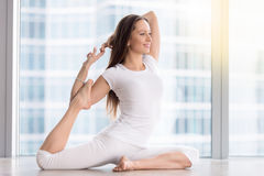 Young woman in One Legged King Pigeon pose, floor window Stock Image