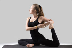 Young woman in One Legged King Pigeon pose, grey studio Stock Photo