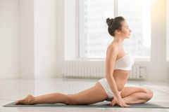 Young woman in One Legged King Pigeon pose, white background. Young attractive woman practicing yoga, doing One Legged King Pigeon exercise, Single leg Pigeon royalty free stock photos