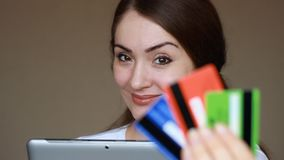 Young woman online banking using tablet computer, shopping online at Internet shop and purchase through credit cards. Portrait of a smiling girl close-up stock footage