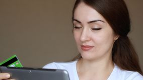 Young woman online banking using tablet computer, shopping online at Internet shop and purchase through credit cards. Portrait of a smiling girl close-up stock video footage