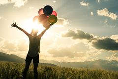 Young woman open arms on grassland with colored balloons Royalty Free Stock Photo