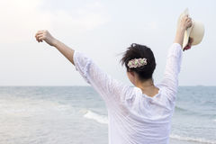 Young woman open arms and holding hat on the beach Stock Photo