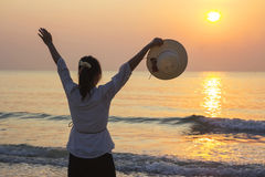 Young woman open arms and holding hat under the sunrise at beach Stock Image