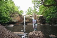 Young woman open arms standing near waterfall. Tourism concept Royalty Free Stock Photography