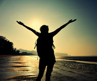 Young woman open arms on sunrise beach Stock Photos