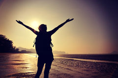 Young woman open arms on sunrise beach Royalty Free Stock Photos
