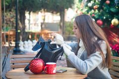 Young woman open her bag in cafe outside. Young beautiful woman sitting in cafe outside, looking for something in her open bag Royalty Free Stock Photography