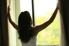 Young woman open window stock image