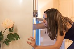 Searching the refrigerator for something to eat. Young woman with opened fridge searching and taking out some food to prepare. What to eat and cook stock photos