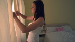 Young woman opening bedroom curtains in the morning stock video footage