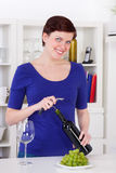 Young woman opening a bottle of red wine in her kitchen. Young woman opening a bottle of red wine in her modern kitchen Royalty Free Stock Image
