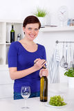 Young woman opening a bottle of white wine in her kitchen Stock Photography