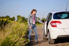 Young woman opening a car door Royalty Free Stock Photos