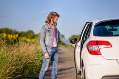 Young woman opening a car door Stock Images
