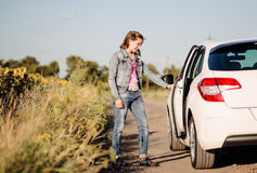 Young woman opening a car door Stock Photo