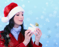 A young woman opening a Christmas gift. Snowflakes surround her Royalty Free Stock Photo