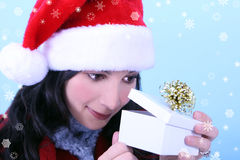 A young woman opening a Christmas gift. Snowflakes surround her Royalty Free Stock Images