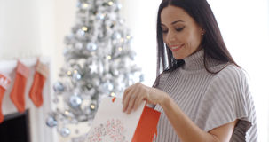 Young woman opening a Christmas gift bag Royalty Free Stock Photo