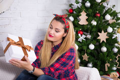 Young woman opening Christmas gift box in decorated living room Royalty Free Stock Images