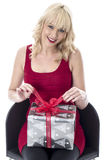 Young Woman Opening a Christmas Present Royalty Free Stock Photos