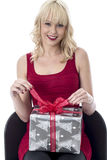 Young Woman Opening a Christmas Present Royalty Free Stock Photography