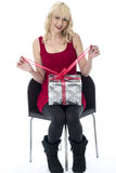Young Woman Opening a Christmas Present Stock Images