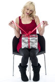 Young Woman Opening a Christmas Present Stock Photos