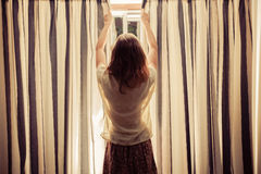 Young woman opening the curtains at sunrise Stock Photography