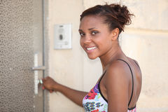 Young woman opening door Royalty Free Stock Image
