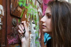 Young woman opening door with key Stock Images