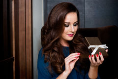 Young woman opening a gift box. Surprise Stock Photography