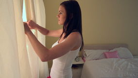 Young woman opening her bedroom curtains in the morning stock footage