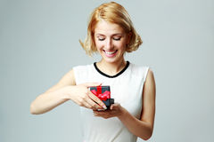 Young woman opening jewelery gift box. Happy beautiful young woman opening jewelery gift box Royalty Free Stock Images