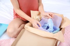 Young woman opening parcel in bedroom at home royalty free stock images