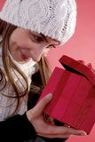 Young woman opening present. Young woman in wintry hat looking in gift box or present; studio background Stock Image