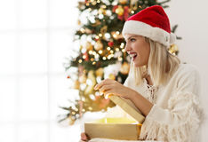 Young woman opening a present on Christmas morning Royalty Free Stock Photography
