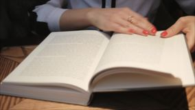 Young woman opening and reading a book  in cozy cafe. Business lady reading a book. Close up view. Studying f stock video
