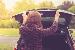 Young woman opening trunk of car Stock Images