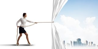 Free Young Woman Opening White Curtain And Presenting Modern City Landscape Stock Image - 109289211