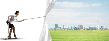 Young woman opening white curtain and presenting modern city landscape Royalty Free Stock Image