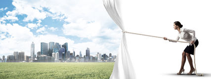 Young woman opening white curtain and presenting modern city landscape Royalty Free Stock Images