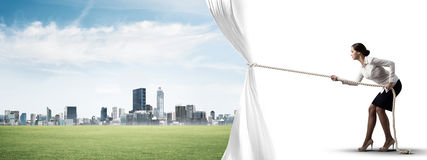 Young woman opening white curtain and presenting modern city landscape Stock Photos