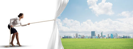 Young woman opening white curtain and presenting modern city landscape Stock Photography