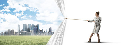 Young woman opening white curtain and presenting modern city landscape Royalty Free Stock Photo