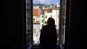 Young Woman Opening Window Morning Italian medieval town. Sanremo, Italy. Apartments and villas for rent. Vacation Europe Travel Tourism stock video footage