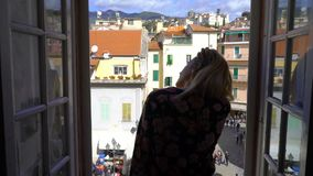 Young Woman Opening Window Morning Italian medieval town. Sanremo, Italy. Apartments and villas for rent. Vacation Europe Travel Tourism stock footage