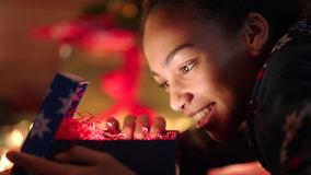 Young woman openning cristmas gift and smiling on new years night stock video footage