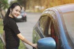 Young woman opens door of blue metallic car Royalty Free Stock Photos